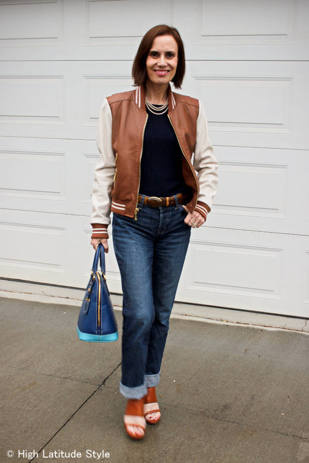 stylist in baseball jacket with boyfriend jeans and sweater