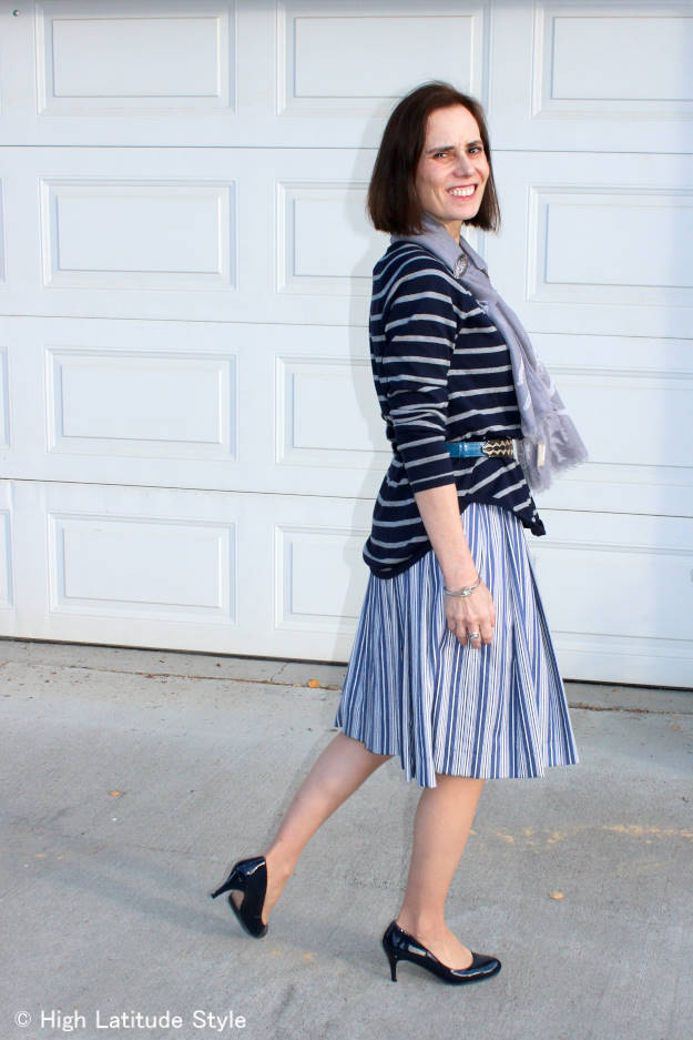 mature fashion blogger wearing a summer dress with sweater as a skirt in autumn