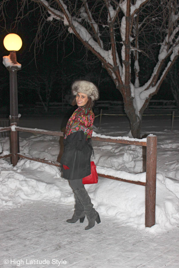 mature fashion blogger in an Alaska winter outfit with shearling coat, boots and Russian scarf