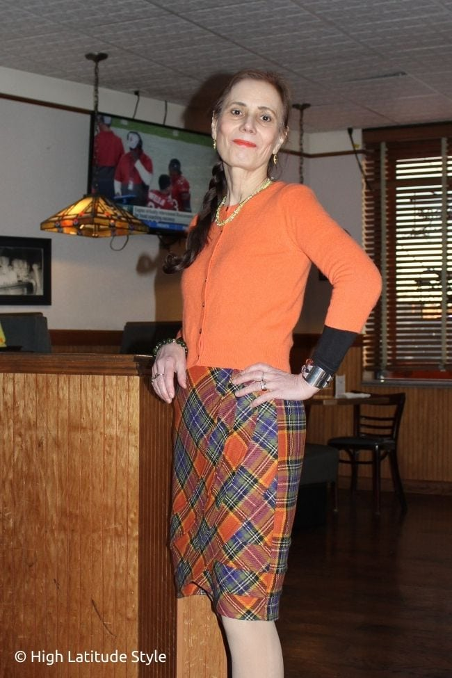 over 50 years old woman in orange cardigan, plaid skirt and nude tights