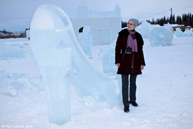 over 50 years old Alaskan style blogger staning in front of giant ice pumps