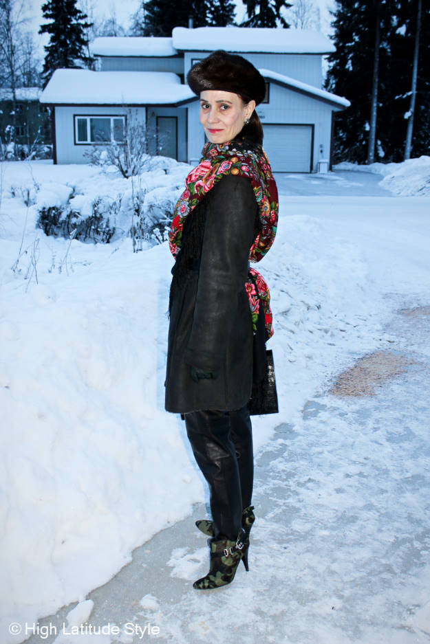 older woman in leather trousers and winter outerwear with Russian scarf and beret