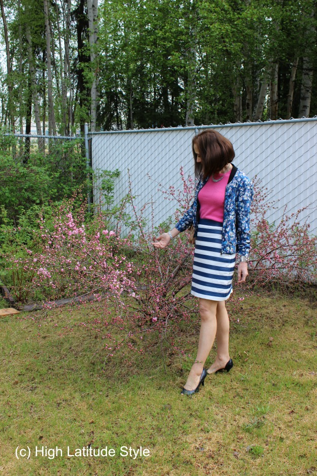 midlife woman in floral bomber with striped skirt