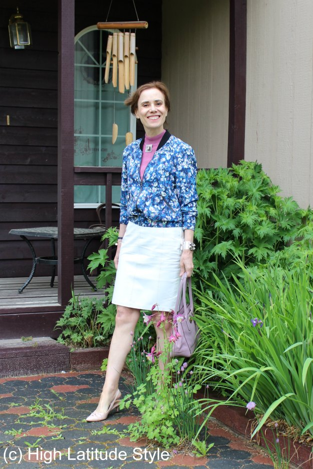stylist in flower print aviator jacket, pink top, white leather skirt