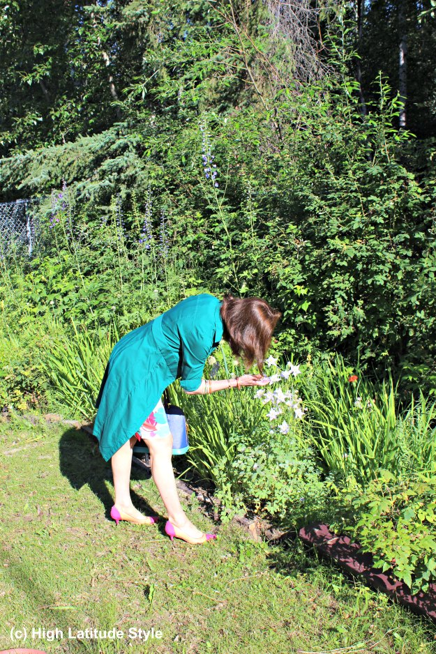 #maturefashion mature woman wearing a dress and picking flowers
