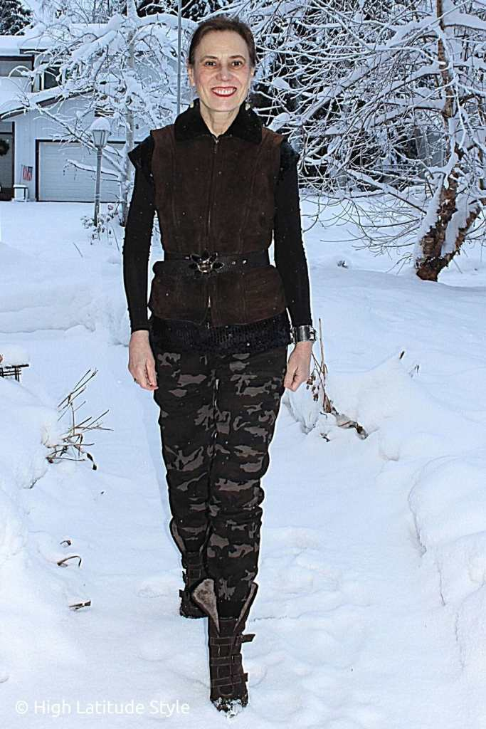influencer in shearling vest, camouflage pants, sequin top, layering top, belt