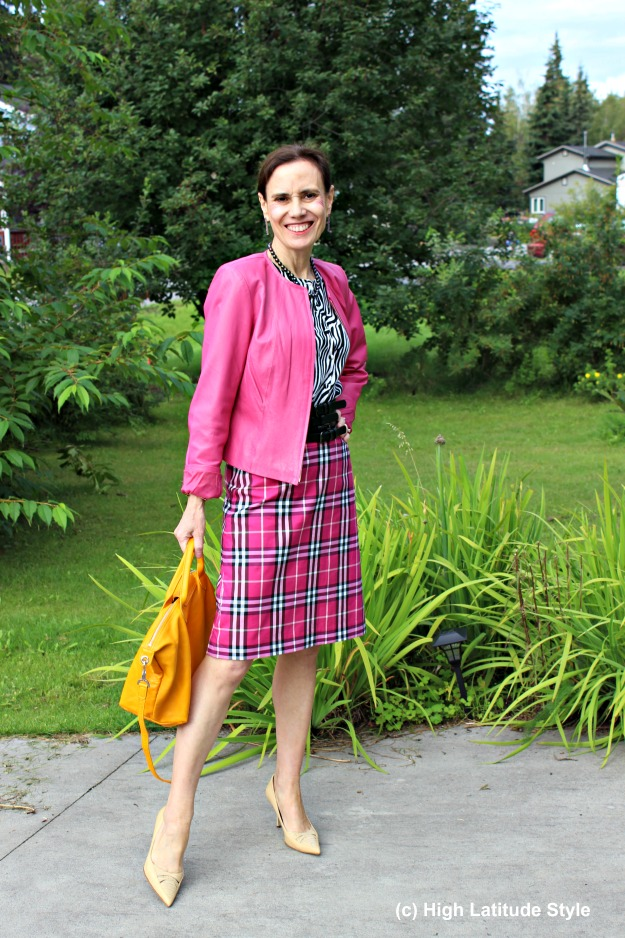 mature woman in fall work outfit with yellow purse, plaid skirt and pink leather jacket