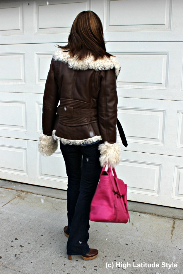 #midlifestyle woman shopping in a shearling motorcycle jacket and flared jeans
