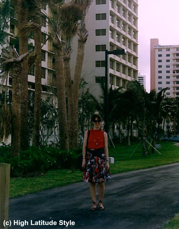 twentysomething woman in abstract print skirt and red top vacation style