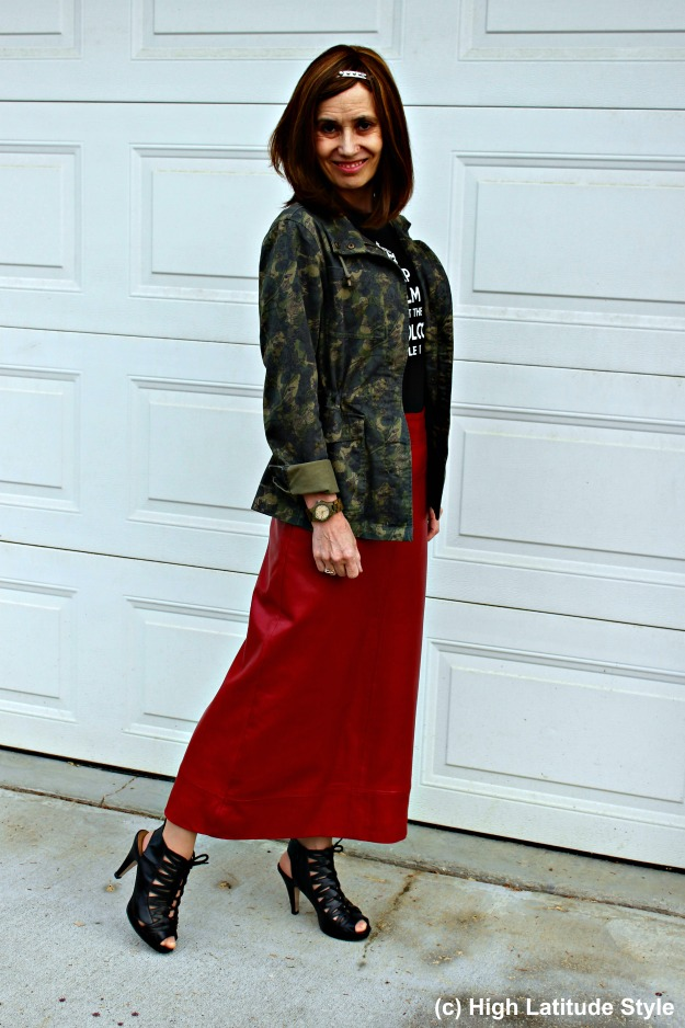 over 50 years old fashion blogger in maxi leather skirt with camo jacket and graphic Tee