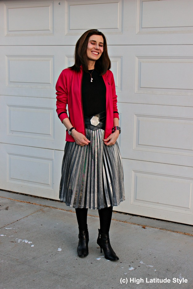 #maturestreetstyle woman wearing a pleated silver skirt with Adidas jacket