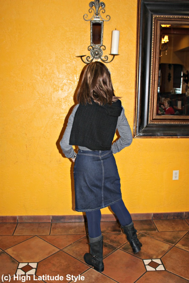 stylish woman over 40 in gray, black and blue winter look with boots