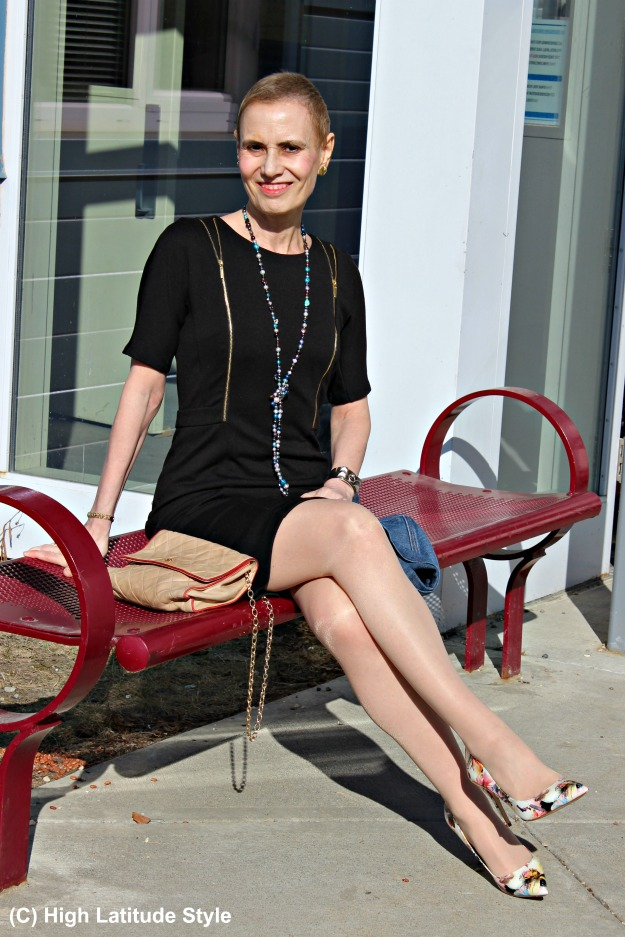fashion over 50 woman sitting in the sun in a black dress