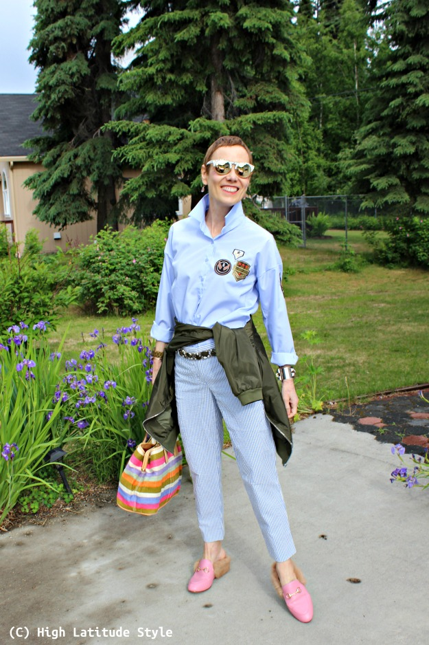 mature woman in casual preppy summer pants, bomber jacket and patch button-down shirt