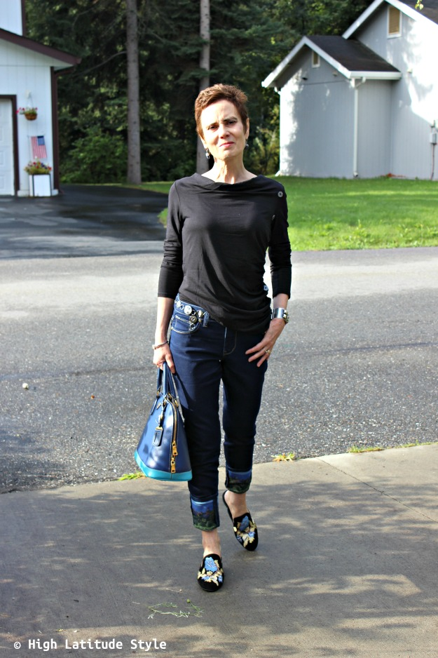 stylist over 50 years old in Soft Surroundings outfit of cuffed jeans, earrings mules and top