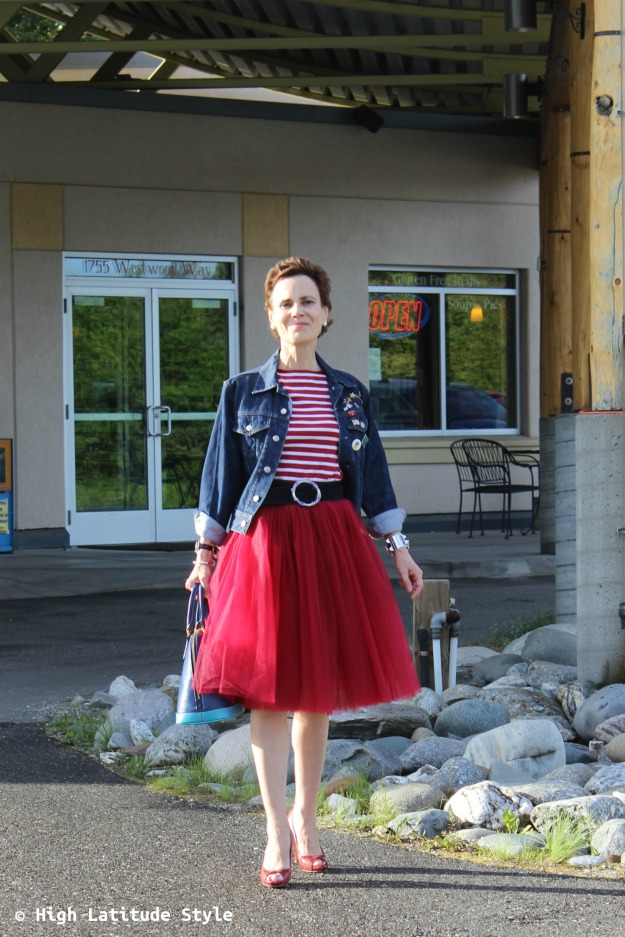 style blogger in red knee-length tulle skirt, knit top, open-toe heels, knit top and denim jacket