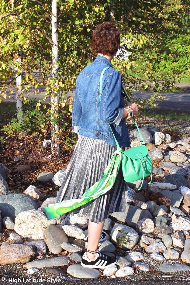 style blogger Nicole with pleated silver skirt, denim jacket green scarf and bag