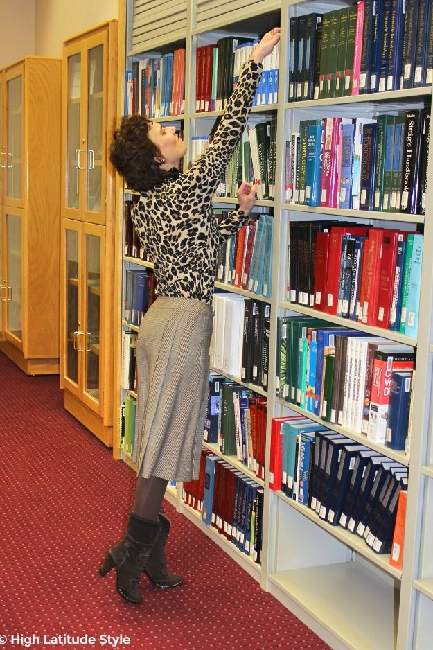 #styleover40 #advancedstyle woman in chic work look taking a book out of a high shelf