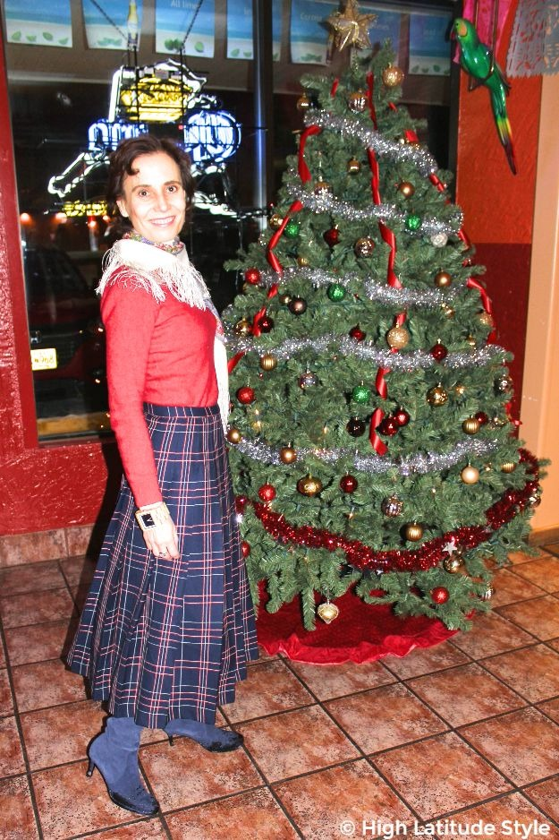 #fashionover40 woman in midi plaid skirt with Russian scarf in front of a Christmas tree