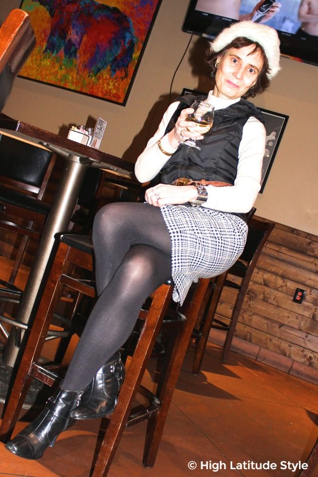 mature woman looking chic in a hounds tooth skirt with down vest outfit