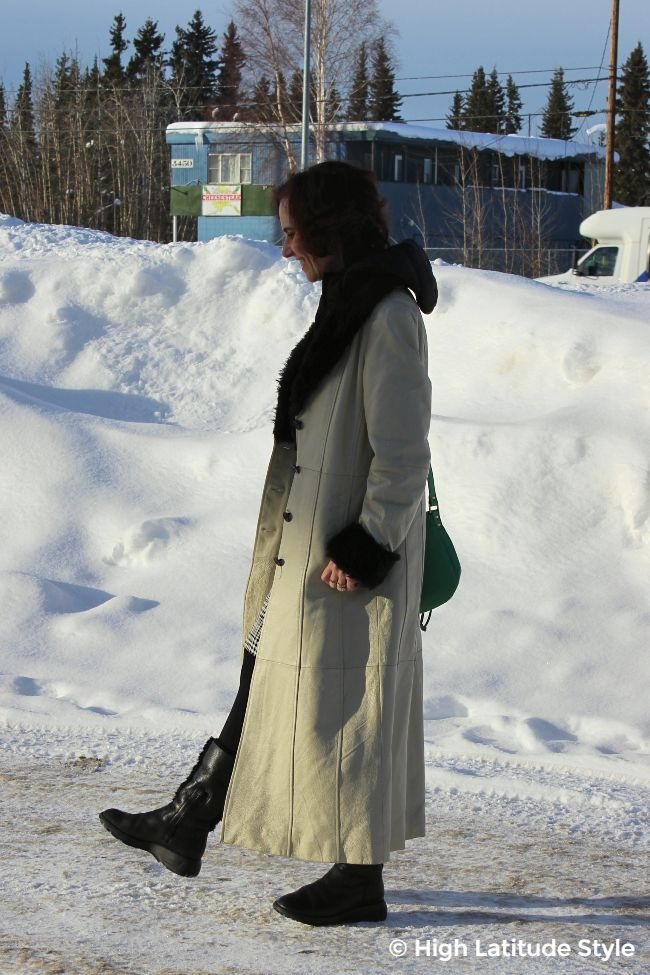 woman in maxi leather coat and grassy bag