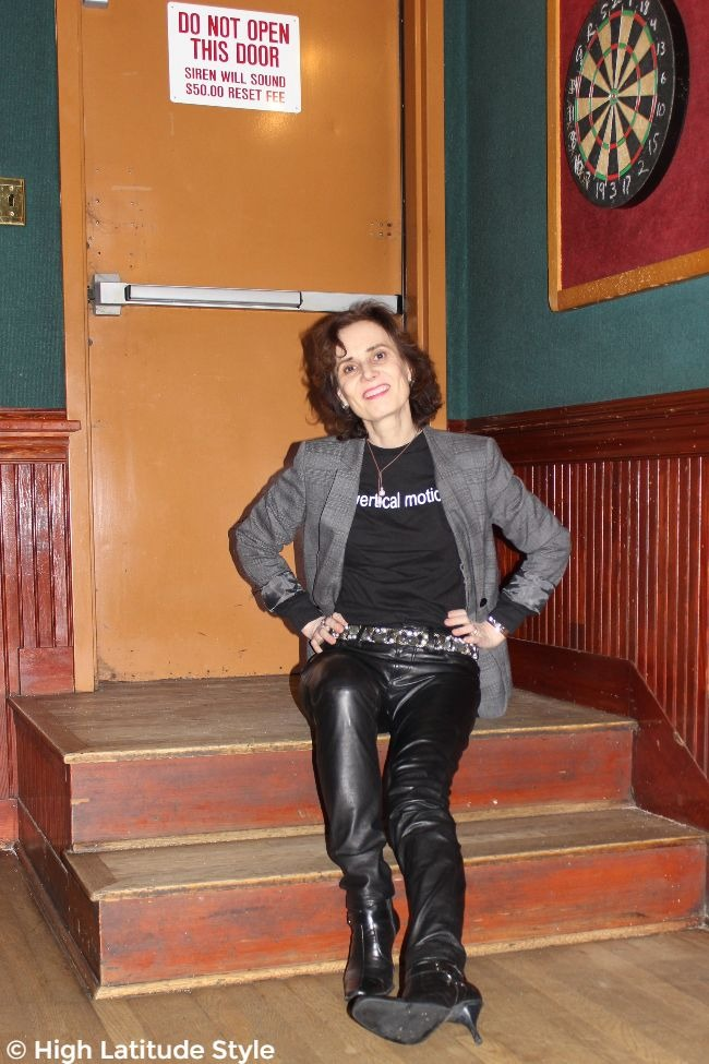 mature fashion blogger sitting on stairs in leather pants, Tee, and blazer
