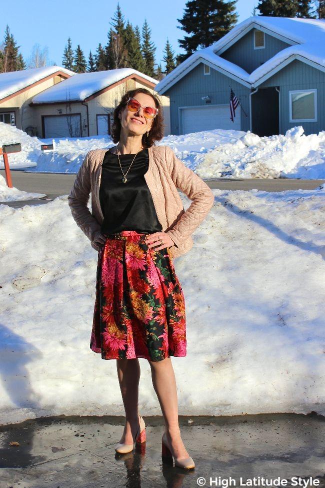 #maturestyle woman in floral skirt, black shirt, nude jacket, green and orange eyewear