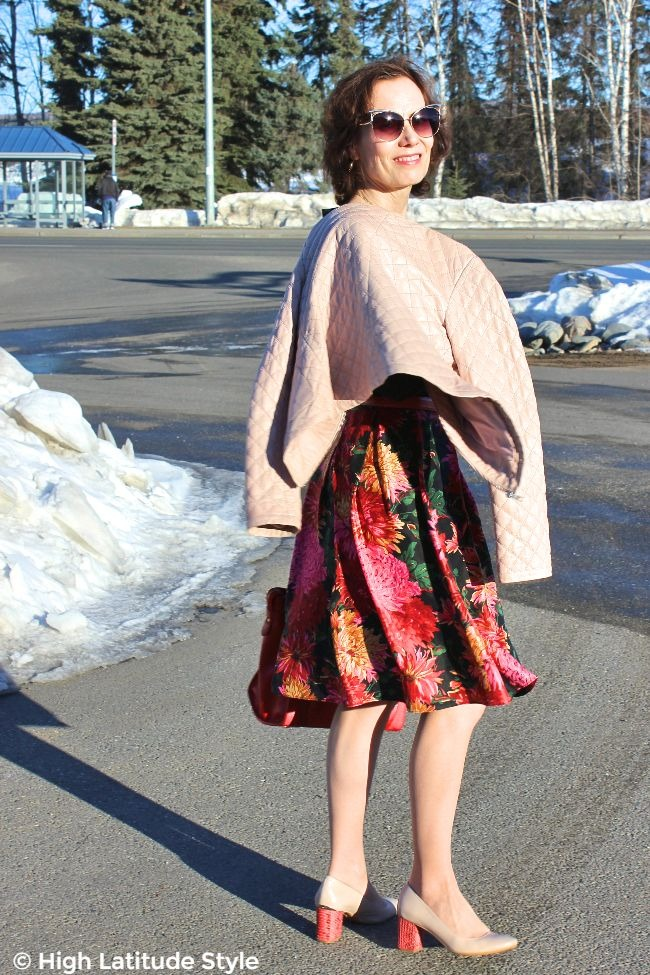midlife blogger in floral skirt, leather jacket and large sunglasses