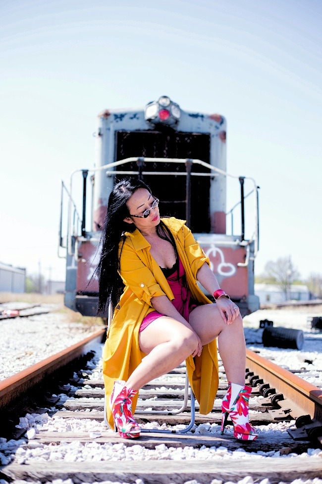 40+ woman in an eclectic street style in yellow, red, black and white in front of a train
