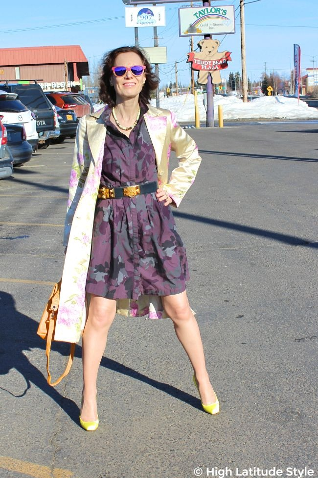 #advancedstyle mature woman in purple gray dress with light yellow pink coat, sunflower yellow bag and neon yellow pumps