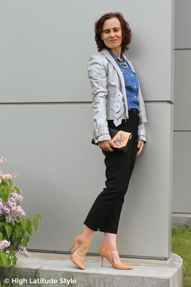 blogger in a silver jacket, pearls, black cropped pants, blue shirt with matching clutch