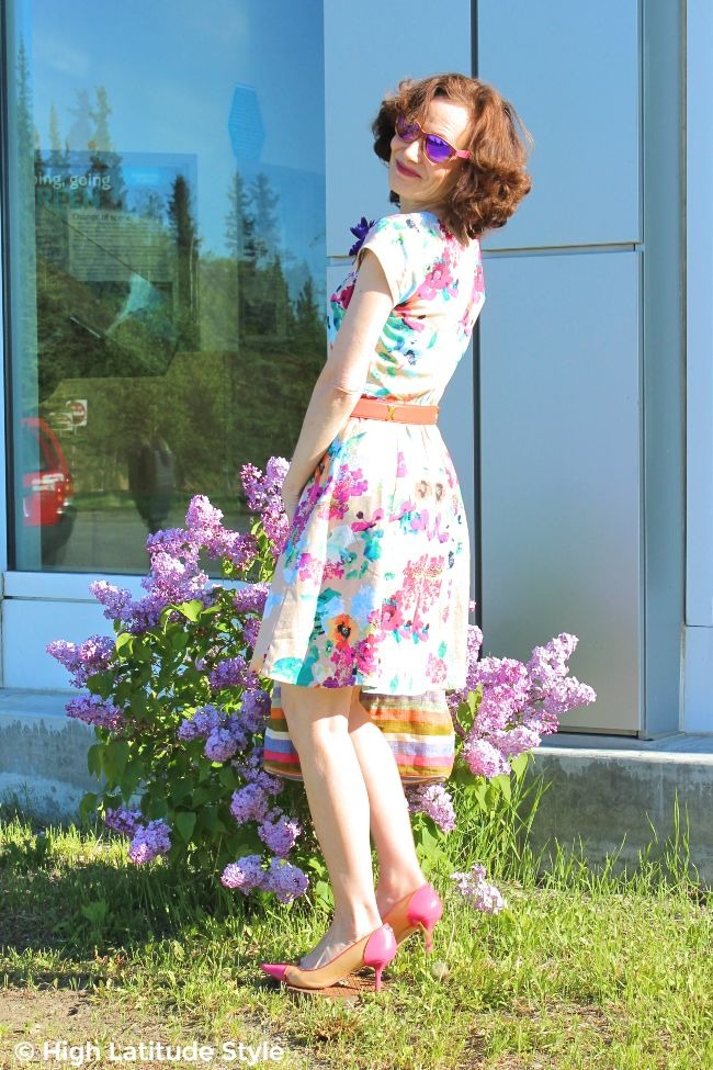 older lady in floral fit-and-flare summer dress with purple mirrored wood sunnies