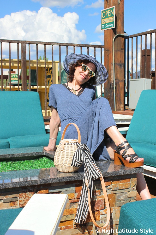 midlife blogger in maxi dress, hat, wood sandals with accessorized trendy basket bag