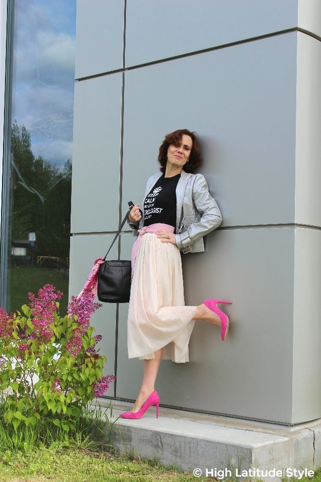 mature street style blogger in blush mesh skirt, pink shoes and belt, graphic tee and silver biker jacket posing at a silver wall