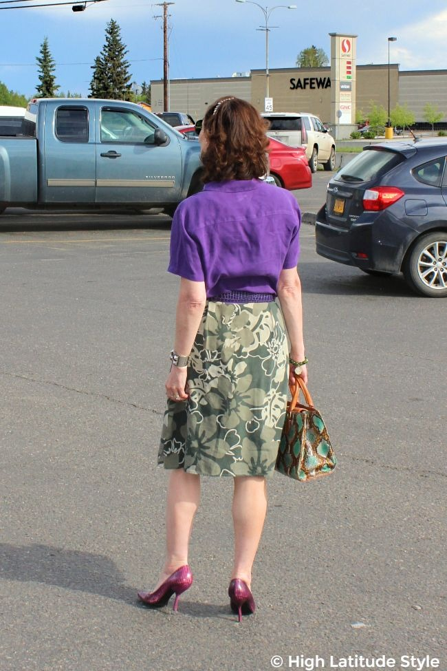 #fashionover50 mildife woman in floral skirt, violet blouse and pumps with snake print work tote