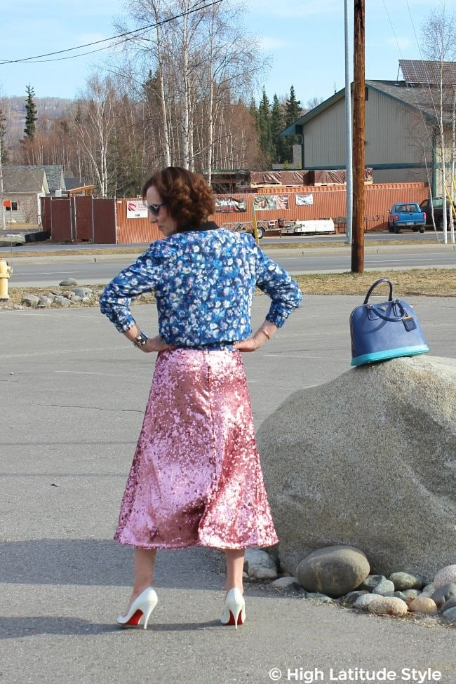 #streetstyleover50 woman donning a street style look with high heels, sequins and floral prink