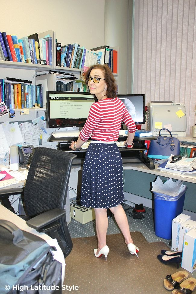#fashionover40 mature woman in striped top, polka dot skirt work outfit with eye protective glasses