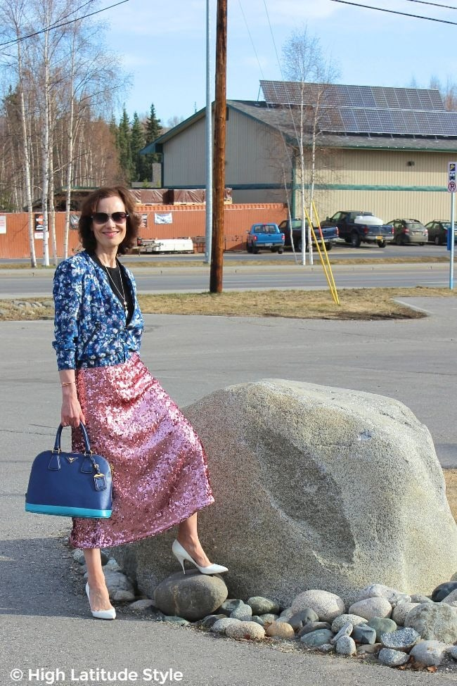 over 50 woman in pink sequin midi skirt, two blue tones bag, white pumps, black top and blue pink white floral jacket