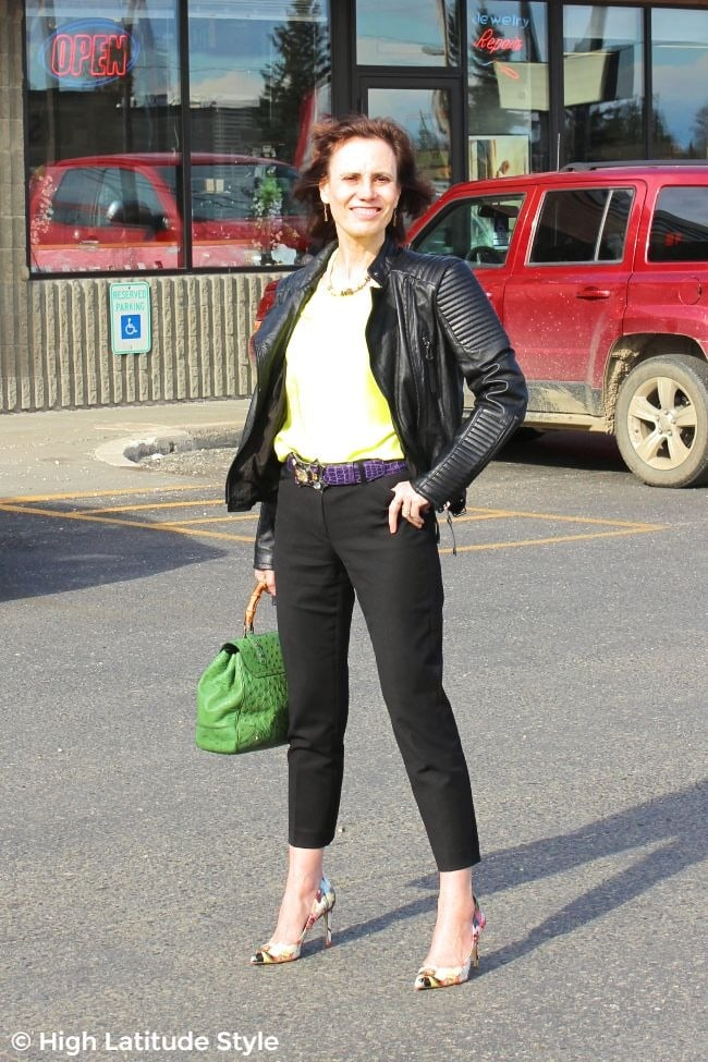 #advancedstreetstyle midlife woman in yellow, black, ultra-violet street chic with colorful belt and pumps