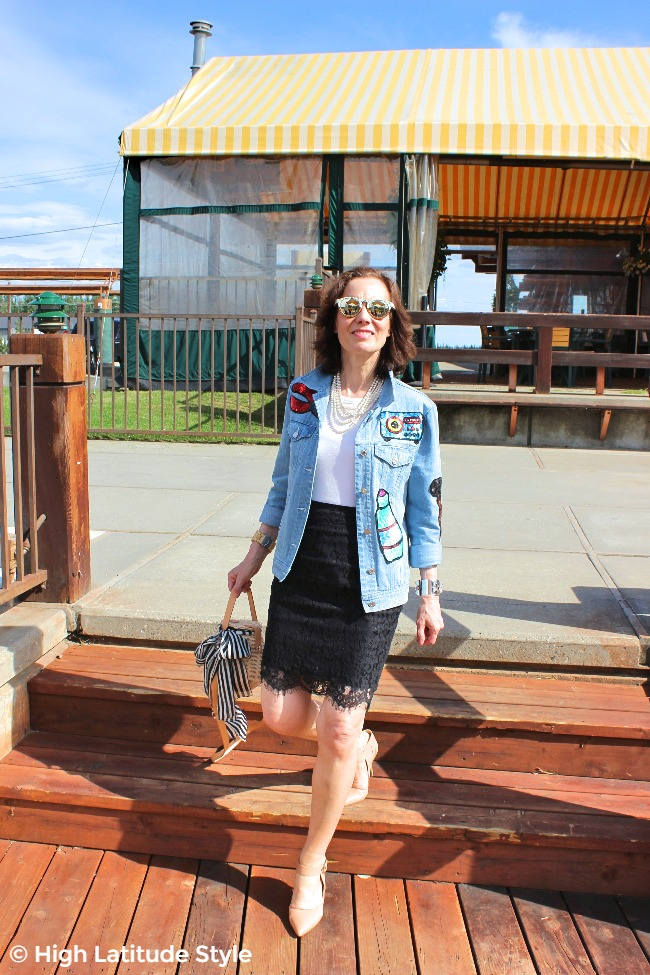 midlife blogger in lace skirt, sequin patch denim jacket, nude pumps and mirrored sunglasses