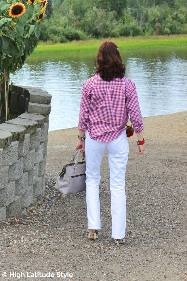 older woman standing at the Chena in white jeans and gingham shirt