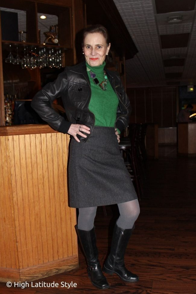 style blogger in bomber jacket riding boots, coarse wool skirt, cashmere sweater