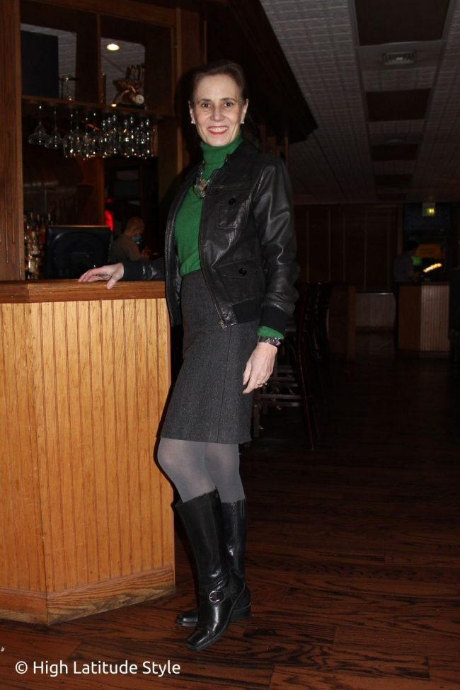 street style blogger in turtleneck sweater, skirt, aviator, riding boots