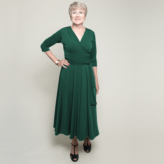 #midlifestyle older woman in forest green faux wrap dress