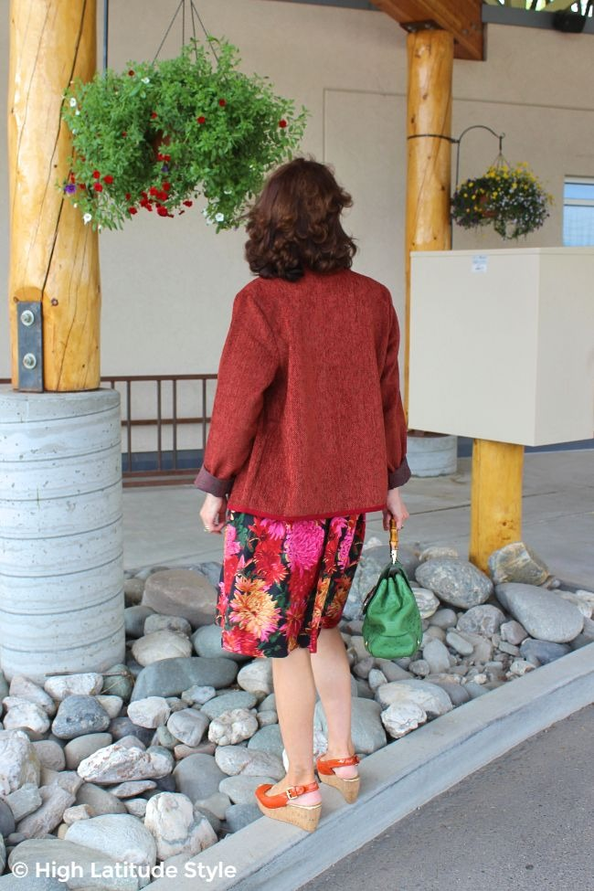 #midlifestyle back view of woman in summer to fall transition outfit with skirt and cooper ruby boxy hip length coat
