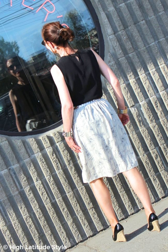 #advancedstyle woman looking into a restaurant wearing a blouse, striped floral skirt and pumps