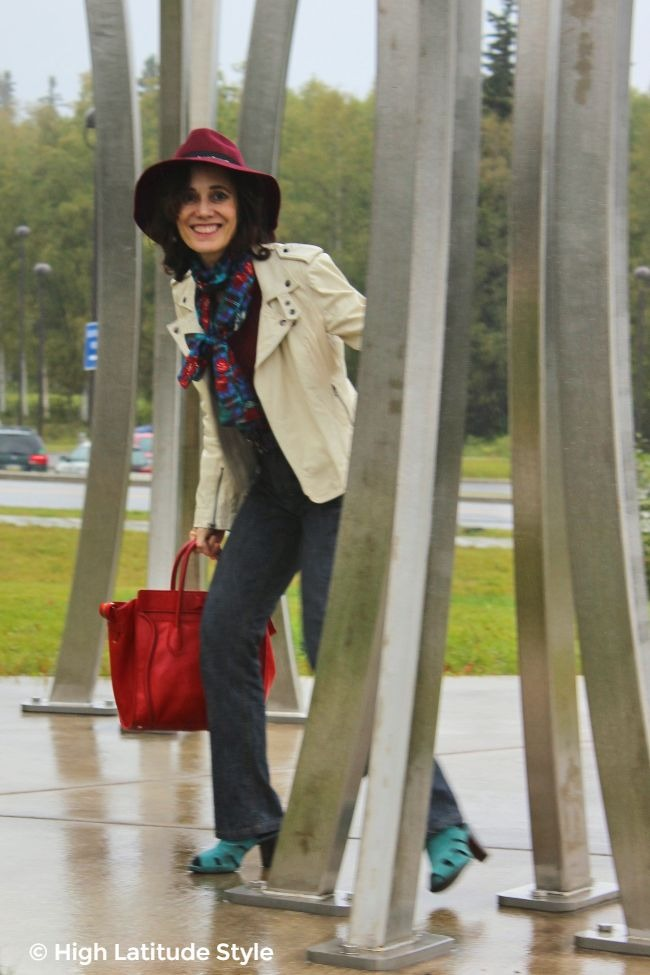 over 50 years old woman in fashion week inspired fall style with biker jacket, scarf, head topper, jeans and sandals