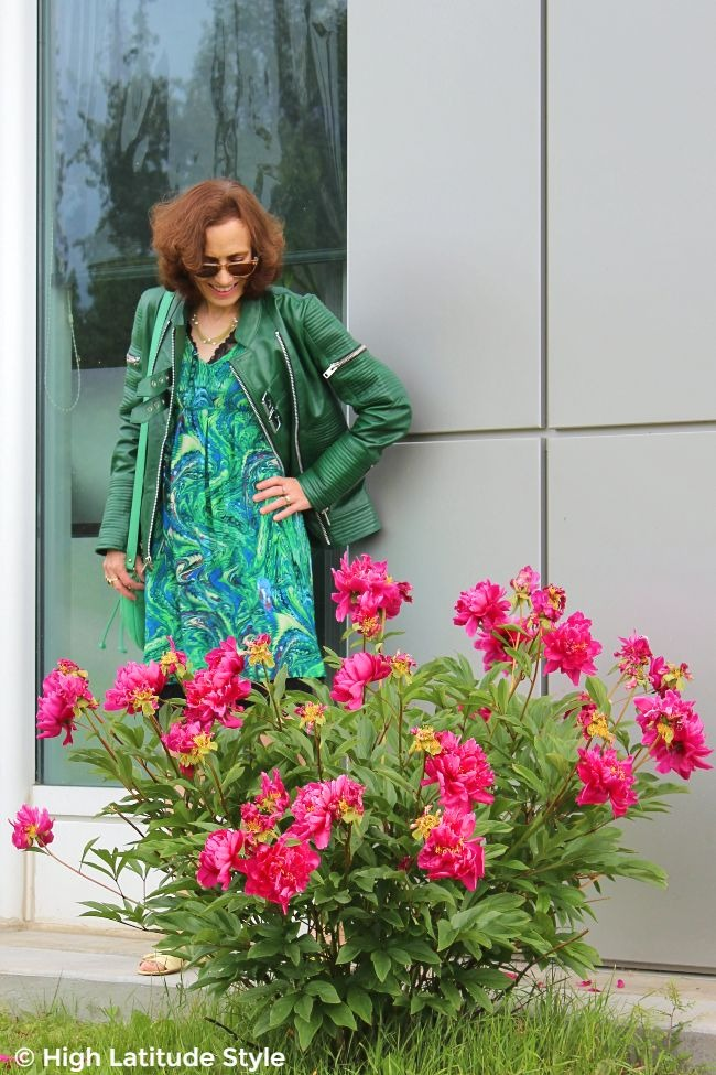 mature woman in green dress, leather jacket, and bag