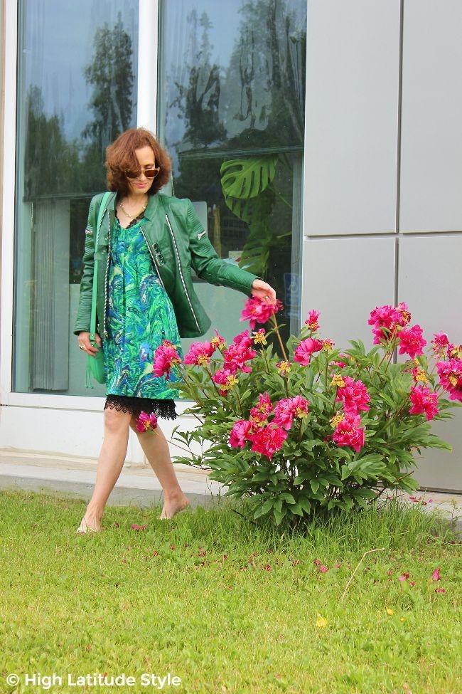 #advancedstyle midlife woman in summer dress with underskirt, biker jacket, slides and shoulder bag
