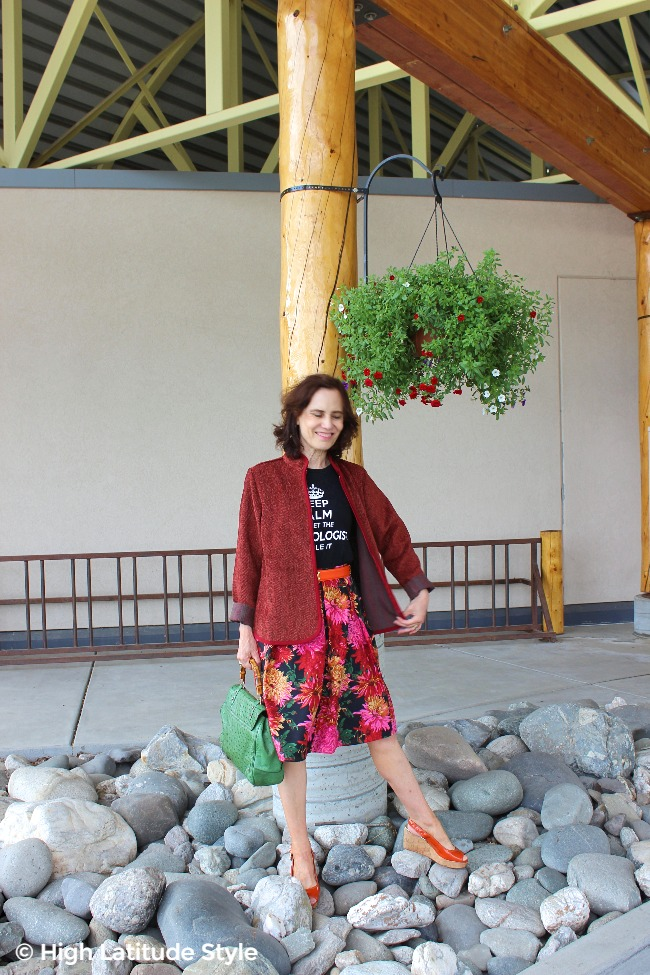 #fashionover50 babyboomer woman in herring bone zipper jacket with floral summer skirt and Tee fall outfit
